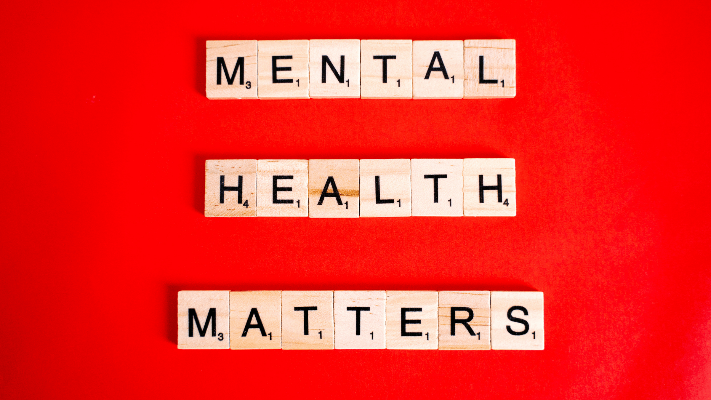Mental Health Matters in wooden scrabble letters on a red background